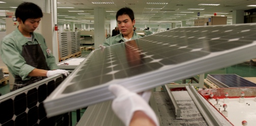 China, Wuxi, Jiangsu Province - Workers assemble solar panels at the Suntech electronics factory. Suntech Power Holdings uses photovoltaic (PV) cell technology to convert sunlight into clean electricity. Credit: Panos / Qilai Shen