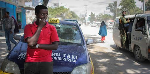 A driver of the Mogadishu Taxi Company waits for a fare outside the company's head office in the Somali capital Mogadishu, September 2013. Operating since the end of May in the city's dusty and once again bustling streets and thoroughfares, the MTC's distinctive yellow and purple cars offer customers taxi fares around Mogadishu at competitive rates and in the first 3 months of operations, the company has increased it's fleet of vehicles from an initial 25 to over 100. The company, according to one of it's drivers, also enables employment opportunities for Somalia's youth following two decades of conflict in the Horn of Africa nation that shattered a generation. AU-UN IST PHOTO / STUART PRICE
