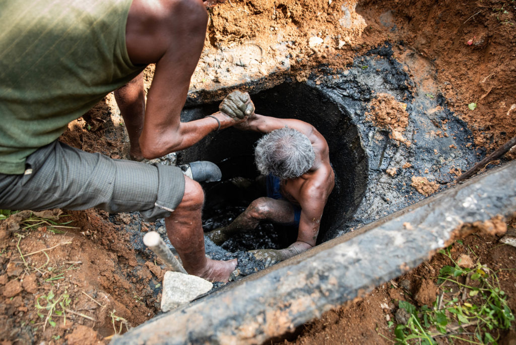 Sanitation workers manually emptying faecal sludge from pits in Bangalore, India